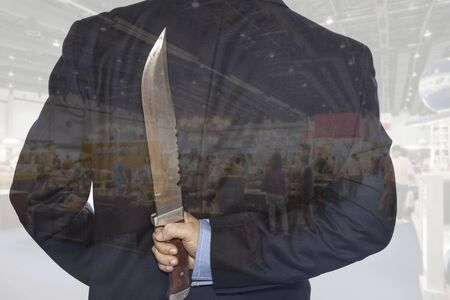 treacherous: Double exposure. Knife hidden behind the  businessman Stock Photo