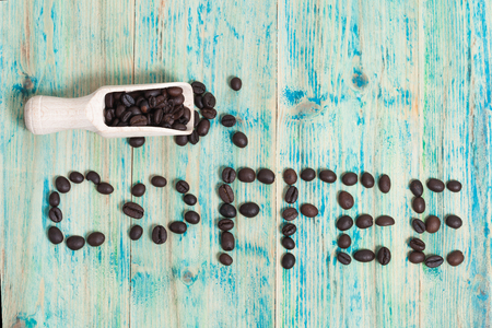 rejuvenate: The word Coffee spelled with coffee beans on wood.