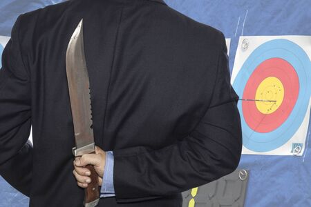 traitor: Knife hidden behind the businessman and target  archery background.