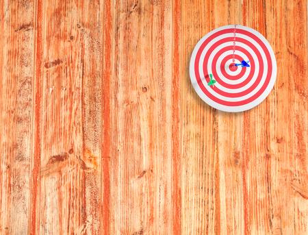 dart on target: dart target on color wood wall Stock Photo