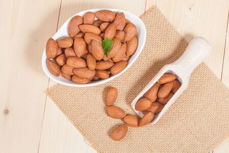 toughness: Almonds in  bowl on wooden background