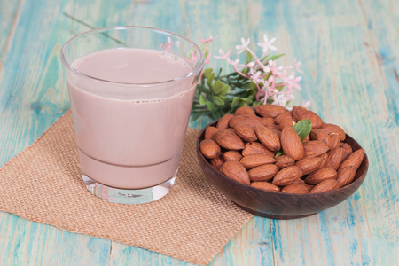 toughness: Almonds in  bowl on wooden background and chocolate milk Stock Photo