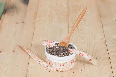 caloric: Chia seeds in bowl with measuring tape.