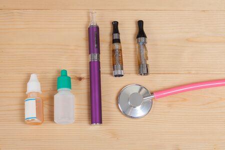 e cigarette: stethoscope and e- cigarette on wood table