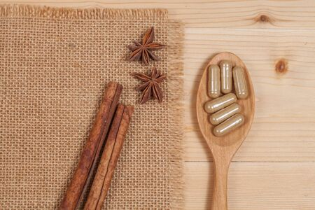 alternative living: Herbal capsules on wooden spoon. herb for healthy  living.
