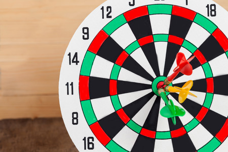 hitting: Dart arrow hitting in bullseye on dartboard