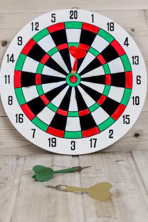 Dart arrow hitting in bullseye on dartboard