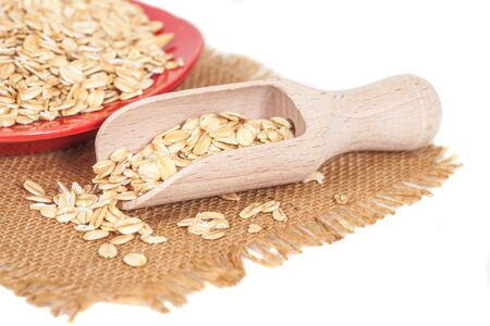Oats flakes pile in wood spoon on white background Stock Photo