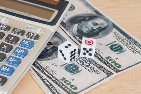 two us dollar: Two dices on wood table with US dollar and calculator