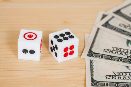 Two dices on wood table with US dollar