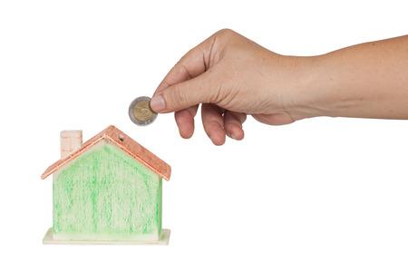 investment real state: mano empujar una moneda en al concepto caja de dinero para la hipoteca o el estado real de la inversión