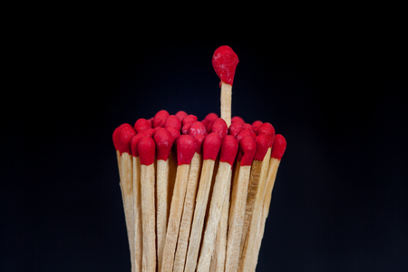 unlit: One matchstick standing over from the group, leader concept Stock Photo