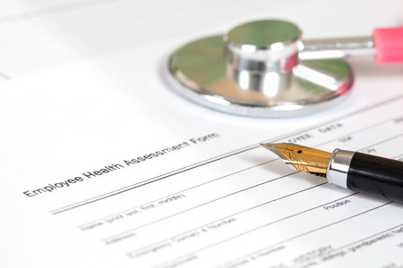 close up employee health assessment form and pen