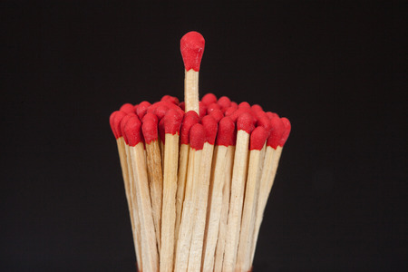 flammable: One matchstick standing over from the group, leader concept Stock Photo