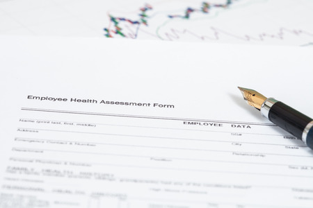 completion: close up employee health assessment form and pen