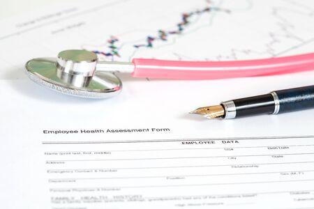 completion: close up employee health assessment form and stethoscope Stock Photo