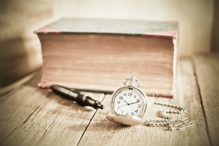vintage pocket clock and old books on wood table