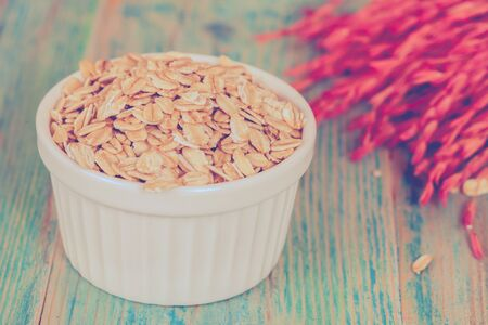 oats flakes pile in bowl on wood background. Stock Photo