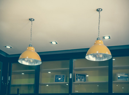 metal filament: A group of hanging lights with shallow depth of field in  class room