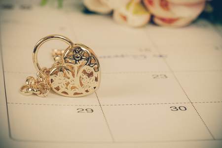 word wedding on calendar and gold bracelet with heart Stock Photo