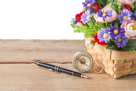 fountain pen and compass with flower plant in basket