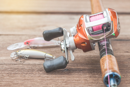 Fishing tackle - Baitcasting Reel, hooks and lures on  wooden background