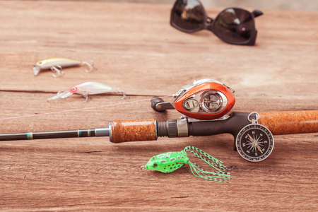 trompo de madera: Fishing tackle - Baitcasting Reel, hooks and lures  on  wooden background