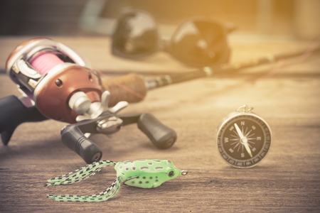 Fishing tackle - Baitcasting Reel,  compass  on  wooden background Stock Photo