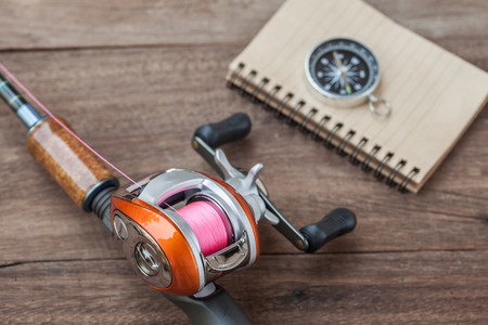 Fishing tackle - Baitcasting Reel, book and compass on  wooden background Stock Photo