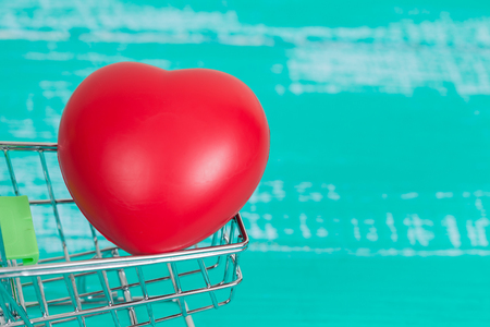 red heart sign in shopping cart on color wood Stock Photo