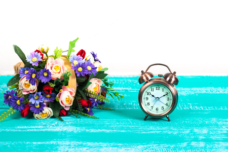 alarm clock with flower basket on wood