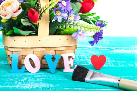 color love letters on wood with flower basket