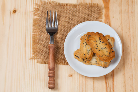 Home made a small sweet cookie with black sesame, typically round, flat, and crisp.Cookie in dish on wood. Stock Photo