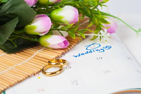 Wedding note on a calendar sets a reminder for the wedding day with flower and duo ring . Stock Photo