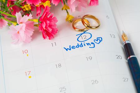 カレンダーのウェディング ノート花とペンと結婚式の日のアラームを設定します 写真素材