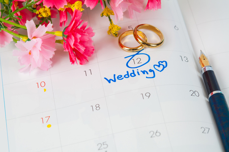 Wedding note on a calendar sets a reminder for the wedding day with flower and pen