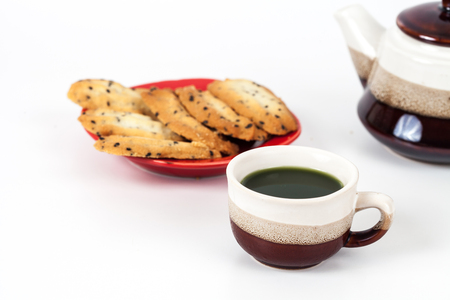 Hot green tea and home made a small sweet cookie with  black sesame, typically round, flat, and crisp.Cookie on  white.