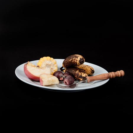 Food waste ,apple ,banana,corn and grape fruit with fork on dish