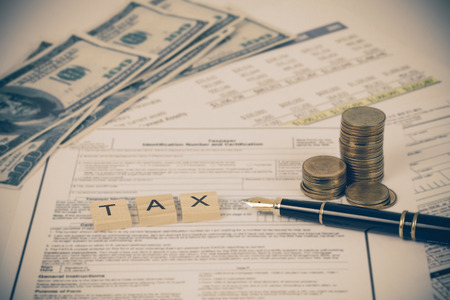 wording tax with tax documents, money on table. Tax concept. Stock Photo