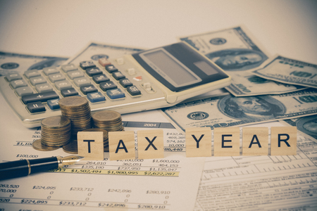 wording tax and calculator with tax documents and money on table. Tax concept.