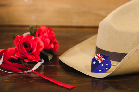 Anzac army slouch hat with red flower on vintage wood background . Stock Photo