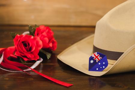 澳纽军团军帽与红色的花在复古的木材背景。