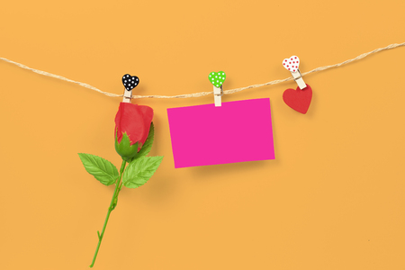 Handmade wood hearts hanging on cloth line or rope with trend color background.clipping path.