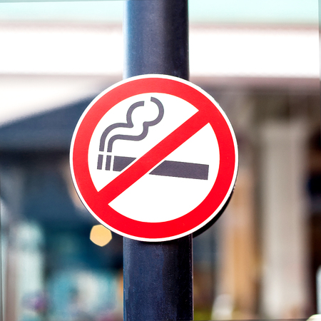 No smoking sign on pole with blur background.
