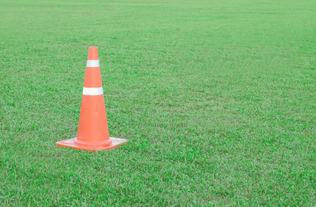 Traffic cone or funnel on green field background.