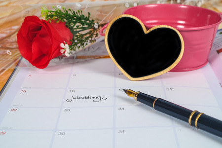 Reminder Wedding day in calendar planning with black heart sign and fountain pen . Banque d'images