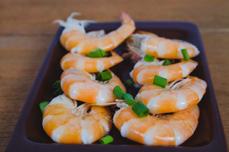 Steamed white shrimp in dish on wood background.