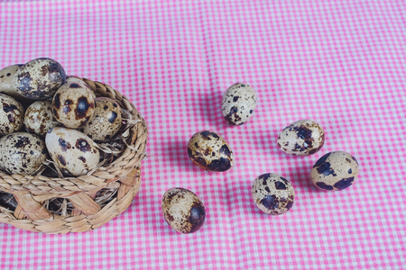 Quail eggs in bamboo basket On the old wood table background.