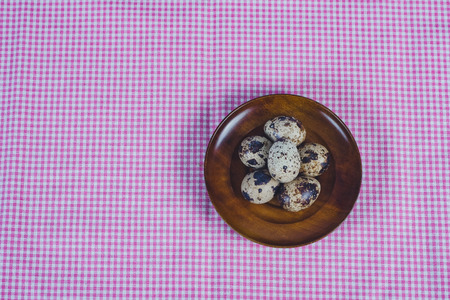 Quail eggs in plate On the old wood table background.