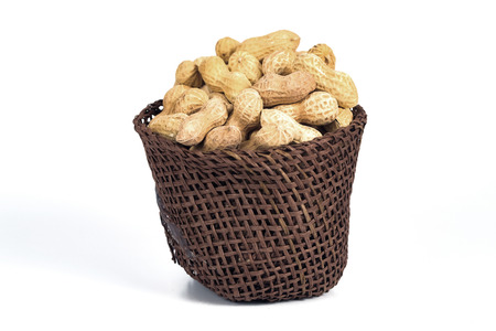 Peanut spill out of basket on background.